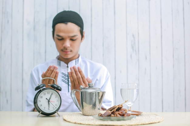 Verschwommenes foto eines jungen muslimischen mannes, der zur iftar zeit zu gott betet
