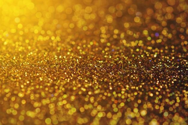 Verschwommenes funkelndes goldfarbenglitterlicht als abstrakter festlicher hintergrund