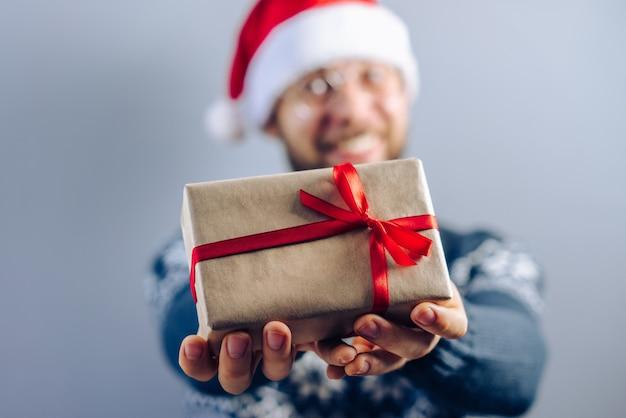 Verschwommenes nahaufnahmebild eines bärtigen kerls, der weihnachtsmann-hut und brillen trägt, die ein geschenk teilen, das in bastelpapier eingewickelt und mit satinrotem band verziert wird