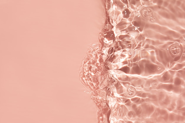 Verschwommenes oder unscharfes transparentes klares wasser rosa flüssig gefärbte klare wasseroberfläche