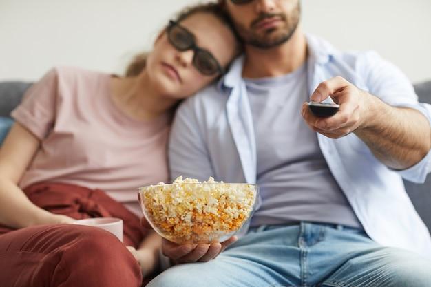 Verschwommenes porträt eines modernen paares, das mit stereobrille fernsieht, während schale popcorn hält, fokus auf vordergrund