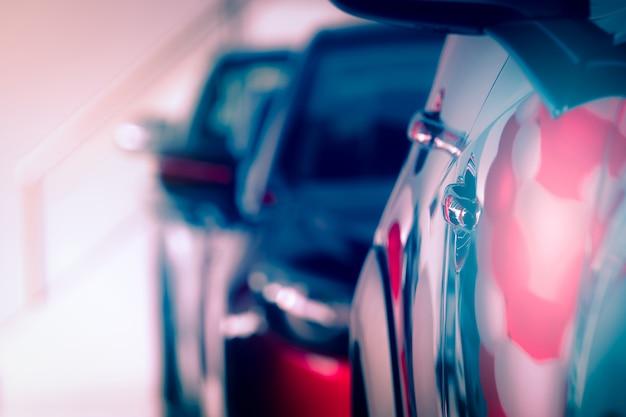 Verschwommenes rotes auto im modernen ausstellungsraum geparkt. autohaus- und auto-leasing-konzept.