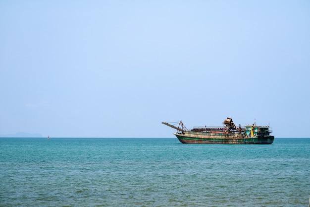 Versenden sie die treibenden boote, die auf horizontlinie im meer schwimmen