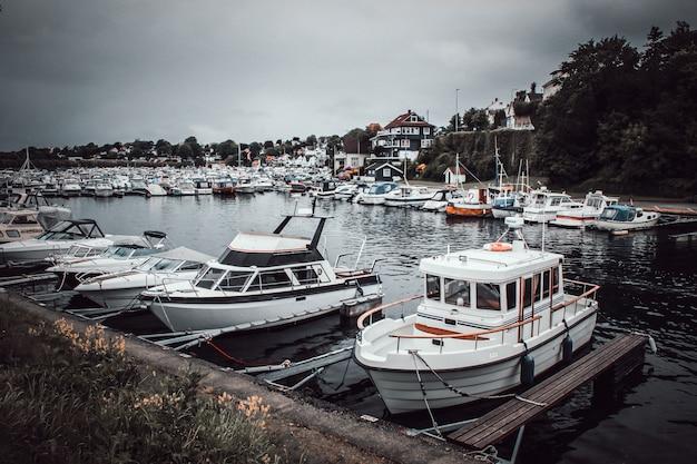 Versenden sie mit hintergrund des bewölkten himmels im hafen, norwegen