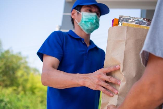 Versender tragen während des ausbruchs des coronavirus eine schutzmaske. asiaten liefern dem käufer das paket vor der haustür. schnelles lieferkonzept