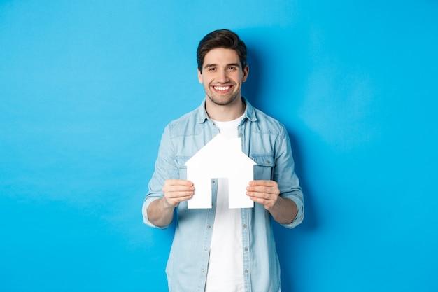 Versicherungs-, hypotheken- und immobilienkonzept. lächelnder junger mann, der hausmodell hält, wohnung zur miete sucht und vor blauem hintergrund steht