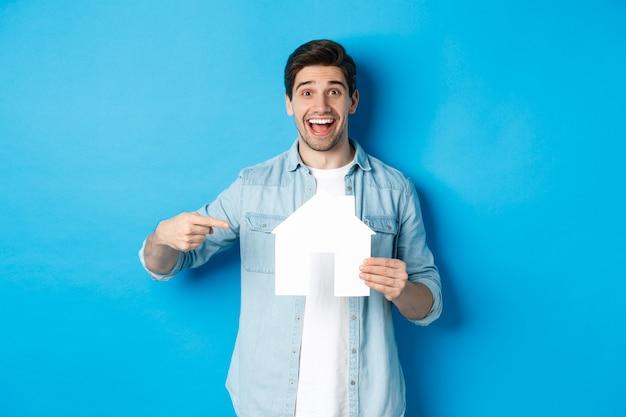 Versicherungs-, hypotheken- und immobilienkonzept. überraschter mann, der auf hausmodell zeigt und lächelt, wohnung sucht, um zu mieten oder zu kaufen, vor blauem hintergrund stehend.