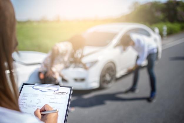 Versicherungsagent, der auf klemmbrett nach unfallautos schreibt.