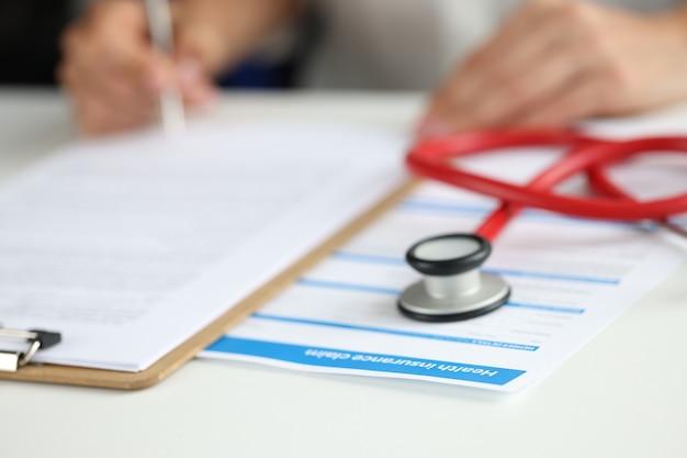 Versicherungsagent füllt krankenversicherungsformular für das konzept der medizinischen dienste des kunden aus