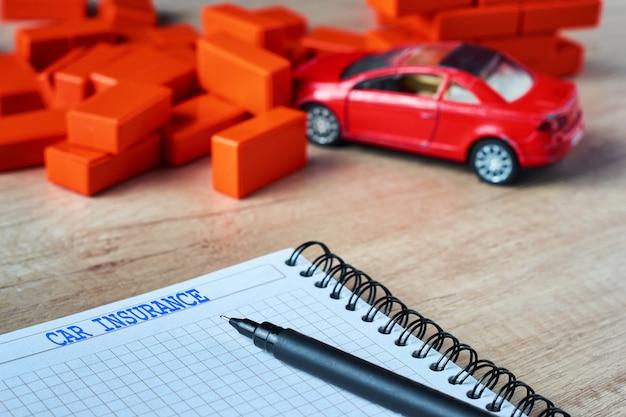 Versicherungsformular und ein unfallauto. kfz-versicherungskonzept