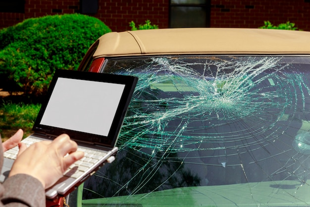 Versicherungsvertreter, der versicherungsfallformular auf laptop nach autounfall, windschutzscheibenabsturz füllt