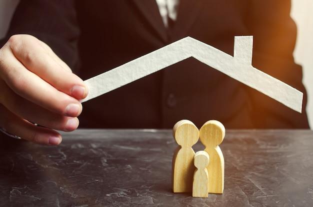 Versicherungsvertreter hält ein haus über der familie. das konzept der versicherung von familienleben und eigentum.