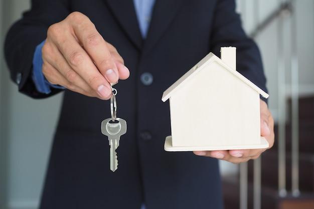 Versicherungsvertreter halten hausmodelle und schlüssel