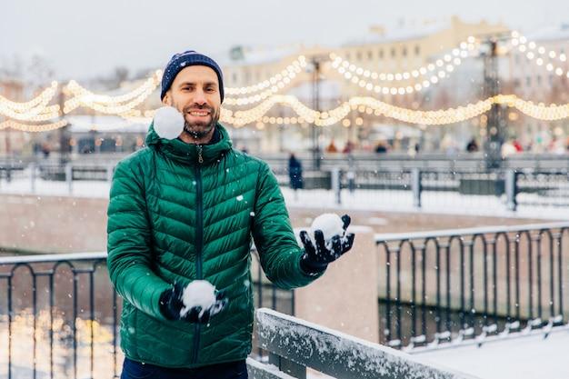 Verspielt lächelnd männliche jonglage mit schneebällen wirft sie in die luft, hat glücklichen ausdruck