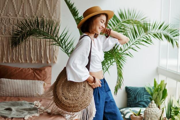 Verspielte böhmische frau, die im stilvollen schlafzimmer mit erstaunlichem interieur, palmen und makramee aufwirft