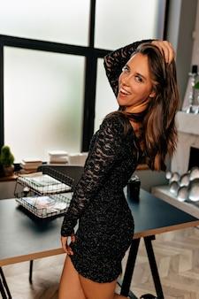 Verspielte charmante frau mit langen glänzenden haaren und hellem make-up, das im schwarzen kurzen kleid aufwirft