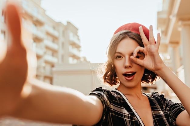 Verspielte französische dame, die auf der straße aufwirft. kaukasisches mädchen in der eleganten baskenmütze, die herum macht, während sie selfie macht.