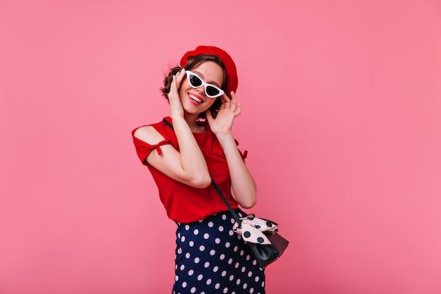 Verspielte französische frau, die in der sonnenbrille aufwirft. ansprechendes dunkelhaariges mädchen in der roten baskenmütze, die auf rosiger wand lächelt.