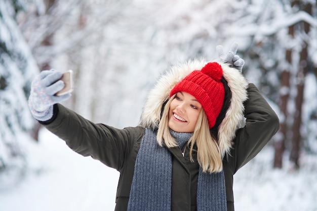 Verspielte frau, die ein selfie im winterwald macht