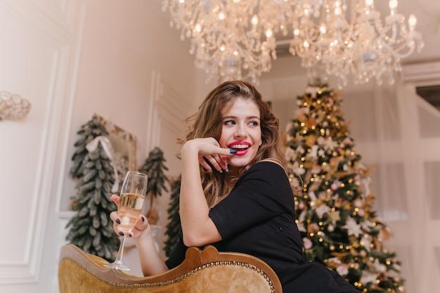 Verspielte frau, die neujahrsferien mit glas champagner genießt. innenfoto des herrlichen lockigen mädchens im schwarzen outfit, das mit charmantem lächeln aufwirft, das im raum mit geschmücktem weihnachtsbaum sitzt.