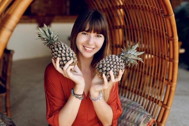 Verspielte frau, die zwei ananas hält und auf hängendem bambusstuhl sitzt