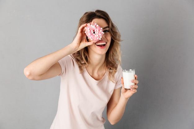 Verspielte frau im t-shirt, die spaß hat, während donut und milch über grau halten