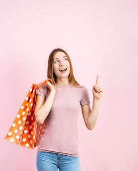 Verspielte frau in jeans mit rosa hintergrund