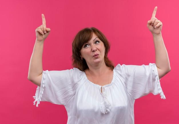 Verspielte frau mittleren alters, die mit den fingern auf isolierte rosa wand zeigt