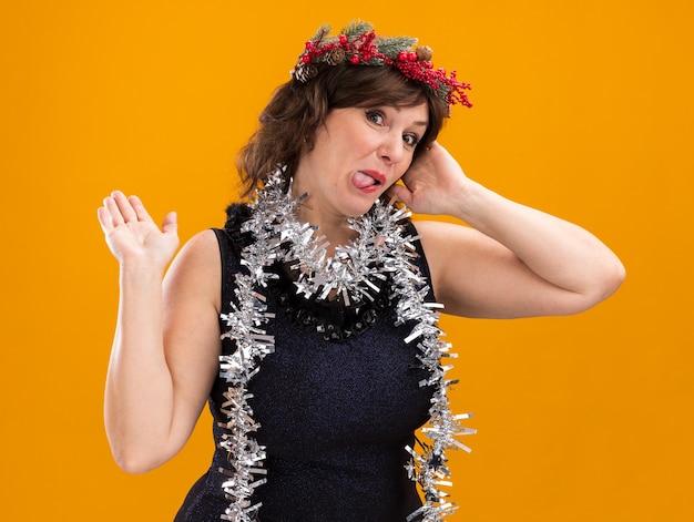 Verspielte frau mittleren alters, die weihnachtskopfkranz und lametta-girlande um den hals trägt, die den berührenden kopf der kamera zeigt, die zunge zeigt, die hinten mit hand lokalisiert auf orange hintergrund zeigt