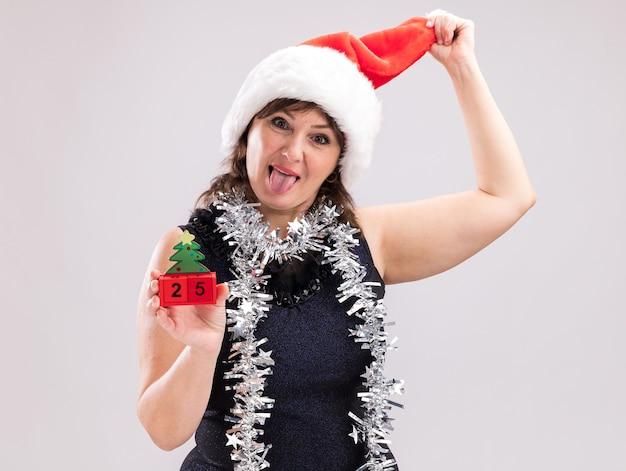Verspielte frau mittleren alters mit weihnachtsmütze und lametta-girlande um den hals mit weihnachtsbaumspielzeug mit datum, das in die kamera schaut, die zunge zeigt und hut isoliert auf weißem hintergrund greift