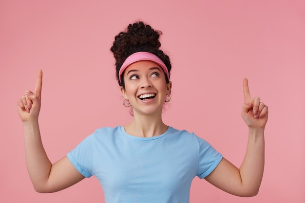 Verspielte frau, schönes mädchen mit dunklem lockigem haarknoten. trägt rosa visier, ohrringe und blaues t-shirt. hat sich geschminkt