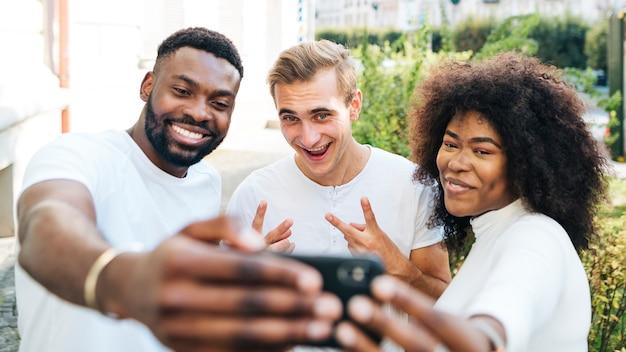 Verspielte freunde im freien nehmen selfie