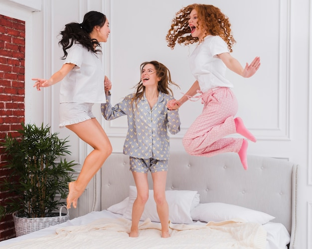 Verspielte freundinnen springen ins bett