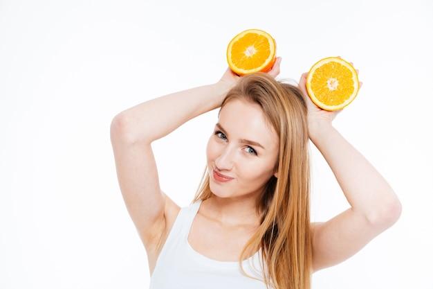Verspielte fröhliche junge frau, die zwei orangefarbene hälften über ihrem kopf auf weißem hintergrund hält holding
