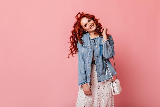 Verspielte junge frau des ingwers, die kamera mit lächeln betrachtet. studioaufnahme des bezaubernden mädchens in der jeansjacke, die glück ausdrückt.