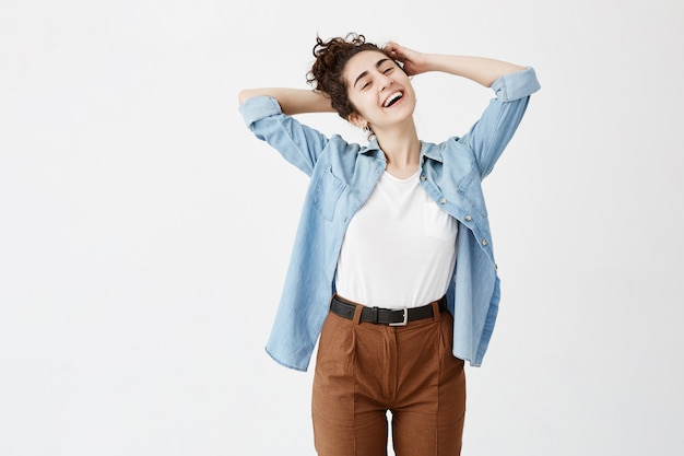 Verspielte junge frau mit dunklem haar im brötchen, jeanshemd mit hochgekrempelten ärmeln lachend über guten witz, ihr aussehen und ausdruck voller freude und glück. menschen- und lifestyle-konzept