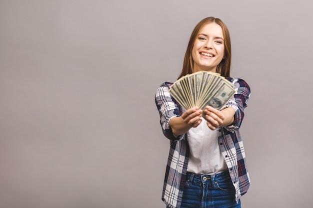 Verspielte junge frau mit langen haaren, die bündel geldbanknoten halten und kamera betrachten