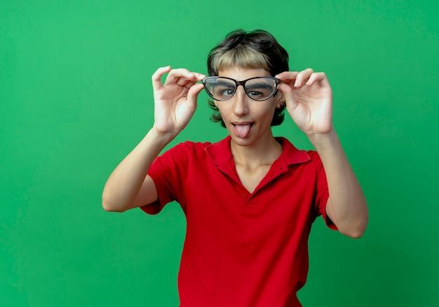 Verspielte junge frau mit pixie-haarschnitt, die brille vorne ausstreckt und zunge zeigt