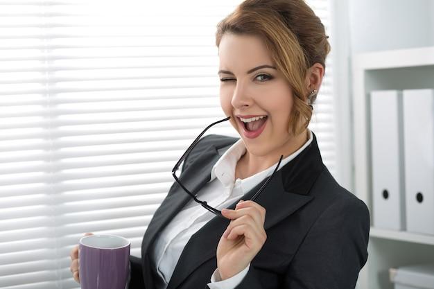 Verspielte junge geschäftsfrau zwinkert, hält ihre brille und schaut. frau, die nahe dem fenster mit einer tasse tee während der kaffeepause steht