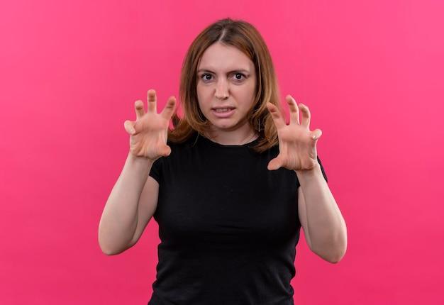 Verspielte junge lässige frau, die tigerpfotengeste auf lokalisiertem rosa raum tut