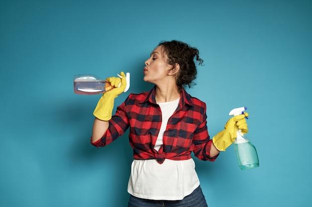 Verspielte junge spanische frau eine hausfrau, die ein reinigungsspray in ihren händen wie eine waffe hält und schießpulver abbläst, als ob nach einem schuss schuss mit weichem schatten