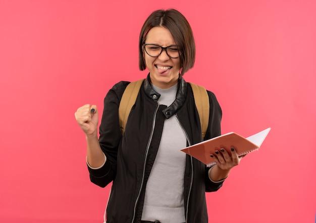 Verspielte junge studentin, die brille und rückentasche hält, die notizblock hält, der zunge mit geballter faust und geschlossenen augen zeigt, lokalisiert auf rosa hintergrund mit kopienraum
