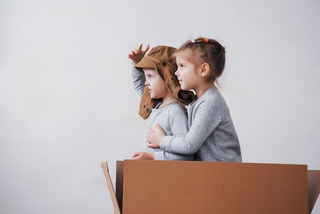 Verspielte kindheit. kleiner junge, der spaß mit pappkarton hat. junge, der vorgibt, pilot zu sein. kleiner junge und mädchen, die spaß zu hause haben