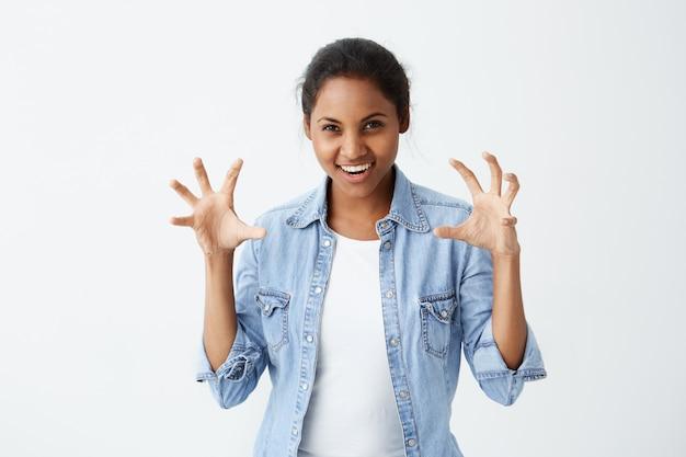 Verspielte, lustige afroamerikanerin mit dunklem haar, lässig gekleidet, zeigt ihre zähne aktiv gestikulierend und versucht, jemanden zu erschrecken. körpersprache.