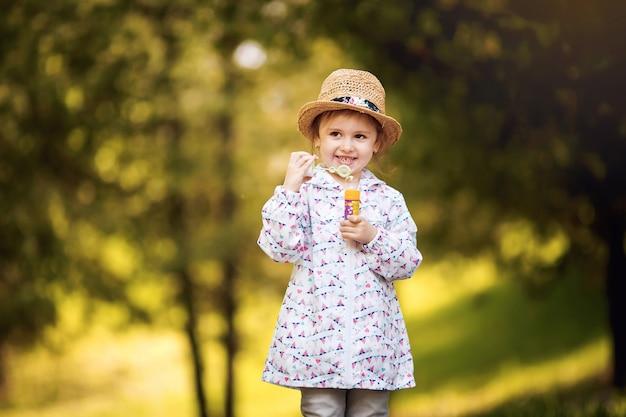 Verspielte schaumblasen des entzückenden glücklichen niedlichen mädchens im grünen spielplatz im sommer draußen. lustiges fröhliches mädchen in den parkglückszeiten. blasen, die seife spielerisch im naturpark blasen.