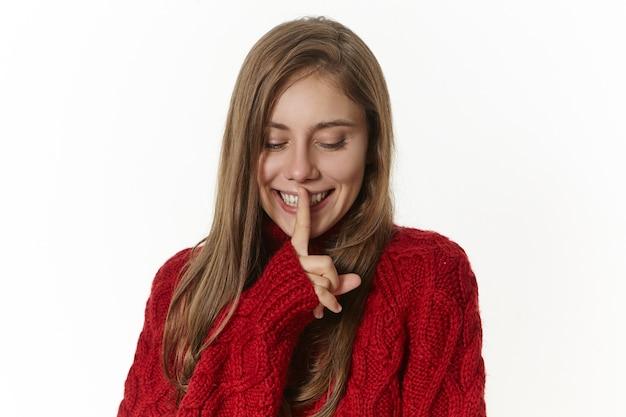 Verspielte schöne junge europäische frau, die zeigefinger auf ihren lippen hält, stilles zeichen zeigt, bittet, still zu bleiben, versucht, geheimnis zu verbergen, geheimnisvoll lächelt und nach unten schaut