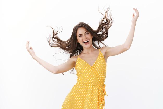 Verspielte, sorglose, lustige, attraktive frau, die die haarsträhne in die luft hebt, amüsiert springt und tanzt, spaß hat, neuen stil liebt, ein tolles sommerkleid kauft, fröhlich lächelt und sich freut, weiße wand