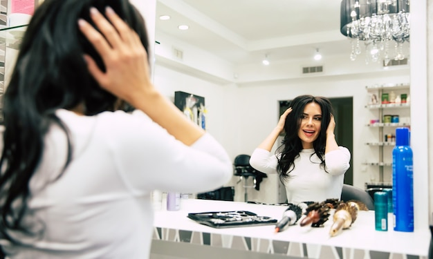 Verspielte stimmung. junge schöne frau schaut in den spiegel, lächelt und berührt ihr haar mit den händen, während sie in einem sessel in einem schönheitssalon sitzt.