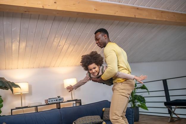 Verspielte stimmung. junger erwachsener afroamerikaner, der eine kleine fröhliche tochter hält, die sich zu hause wie ein flugzeug bewegt