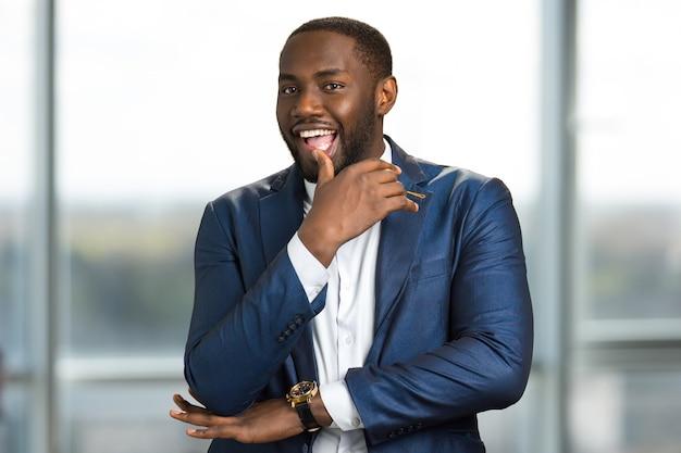 Verspielter amerikanischer geschäftsmann. junger schwarzer geschäftsmann mit einem faszinierenden lächeln